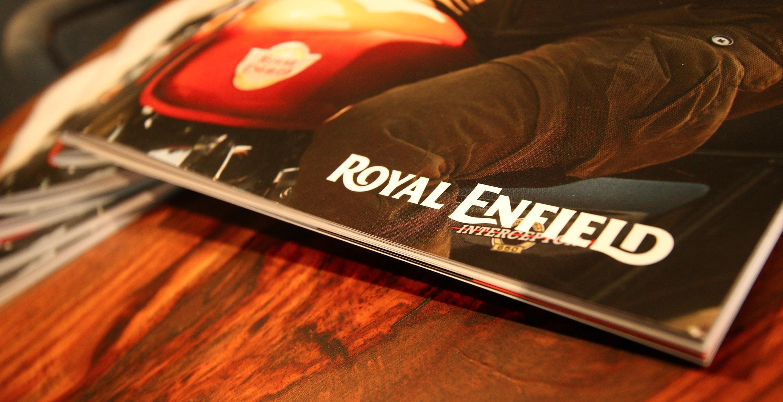 Detalle de catálogo de moto de la marca Royal Enfield sobre mesa de madera