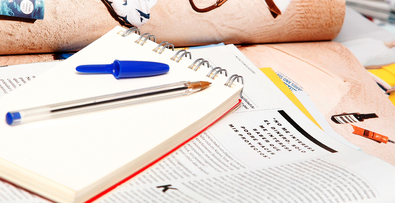 Bloc de notas y boligrafo con revistas de fondo