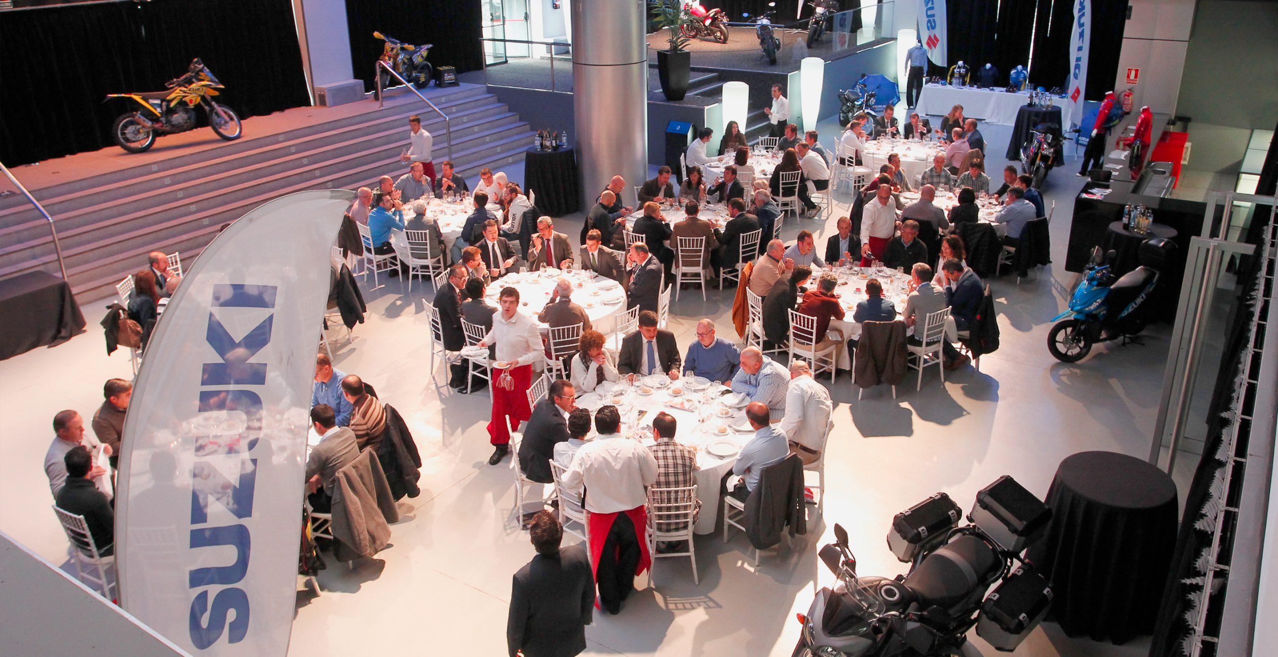 Personas sentadas en vaias mesas en el Teatro Multiespacio Goya con banderola y motos Suzuki