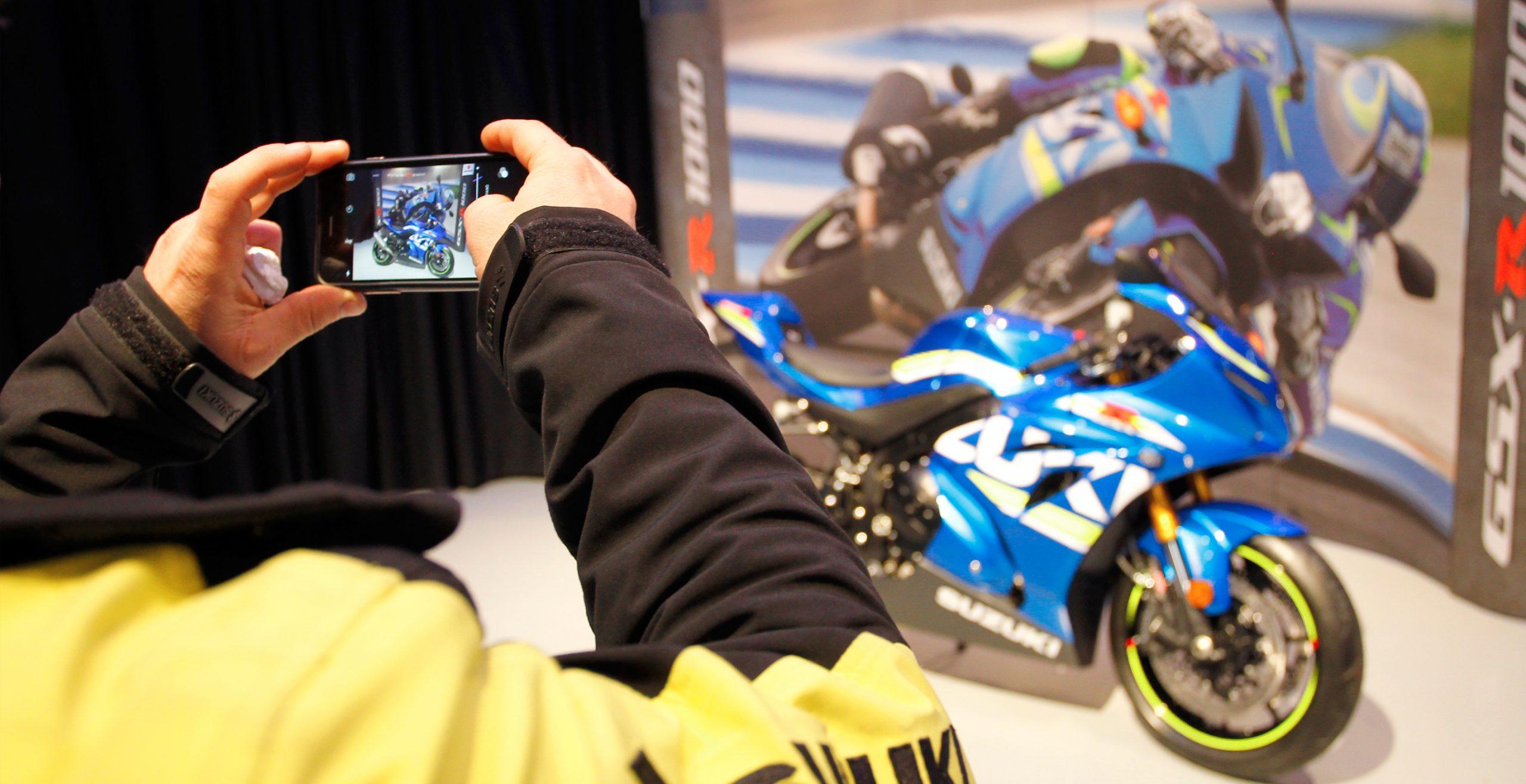 Persona haciendo foto con el móvil a uma moto Suzuki