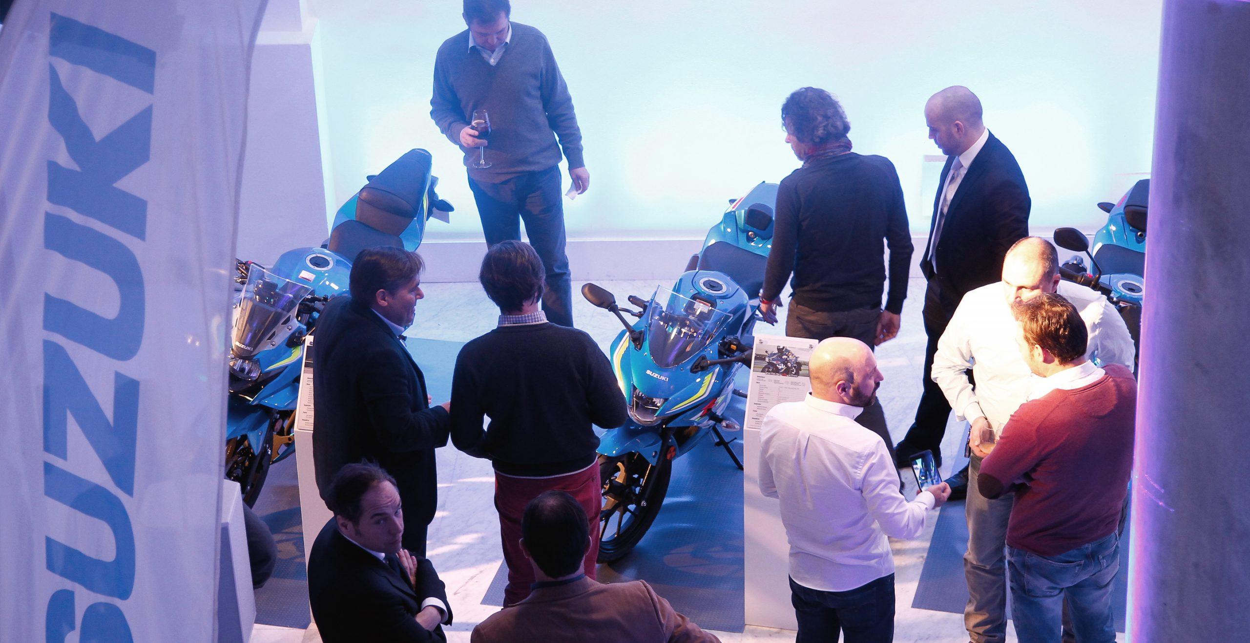 Personas hablando con moto y banderola Suzuki