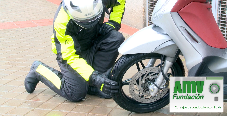 Motorista con traje de lluvia y casco comprobando la rueda delantera de la moto y logotipo de Fundación AMV