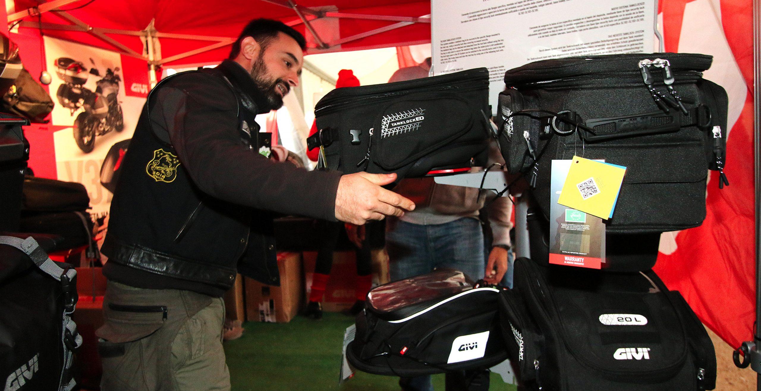 Motorista colocando bolsa sobre depósito en expositor durante la acción de GIVI en Pingüinos 2020