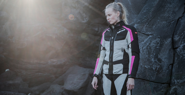 Motorista con conjunto Allroad para mujer de SPIDI en color blanco, negro y rosa