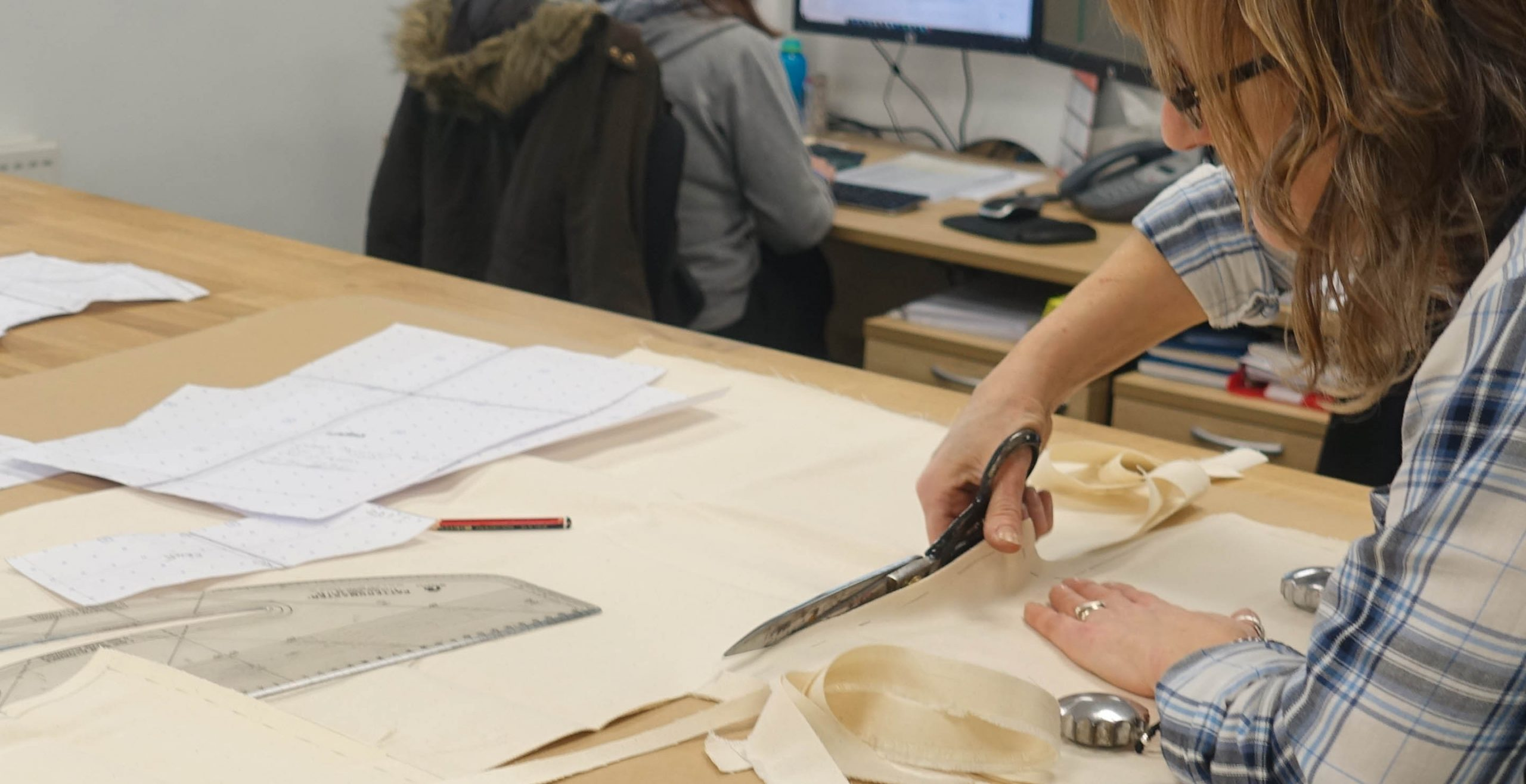 Sastre de RST realizando diseños de patrones, corte y confección de prendas de la marca británica, durante la visita de los periodistas y medios españoles