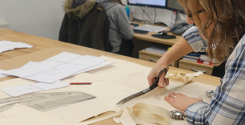 Imagen de acción en la que se aprecia a una trabajadora de RST realizando diseños de patrones, corte y confección de prendas de la marca británica, durante la visita de los periodistas y medios españoles