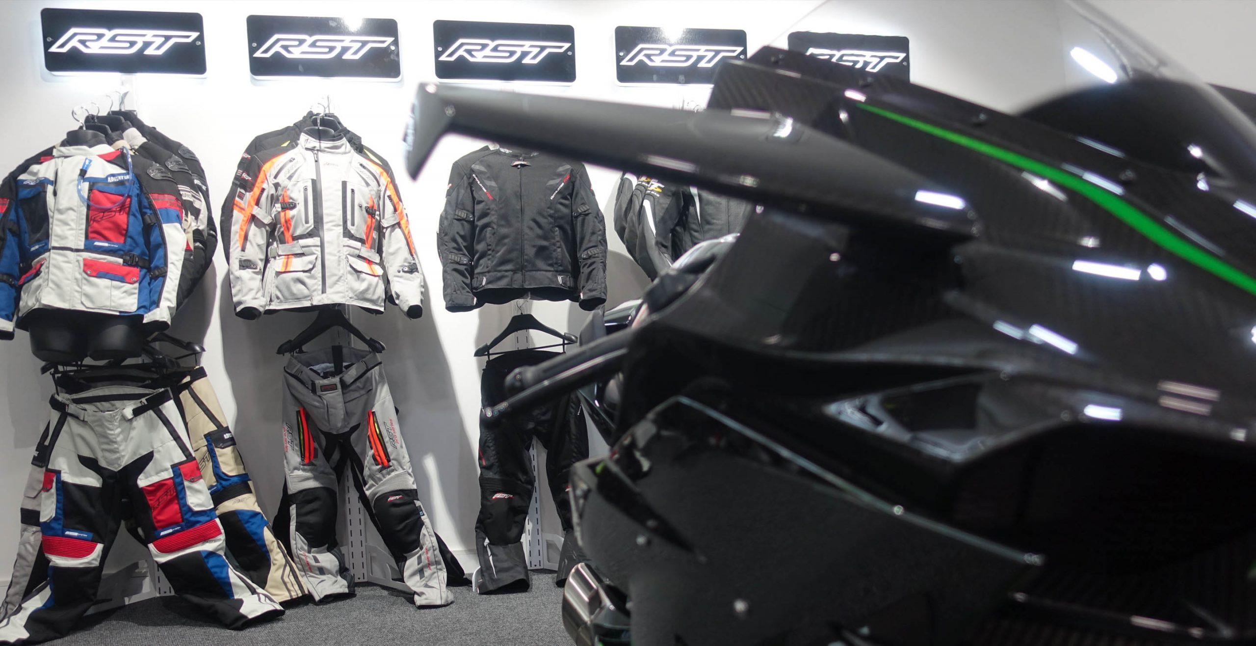 Showroom de RST donde se aprecia en un primer plano una moto de atrezzo delante de la colección de chaquetas adventure y urban 2019