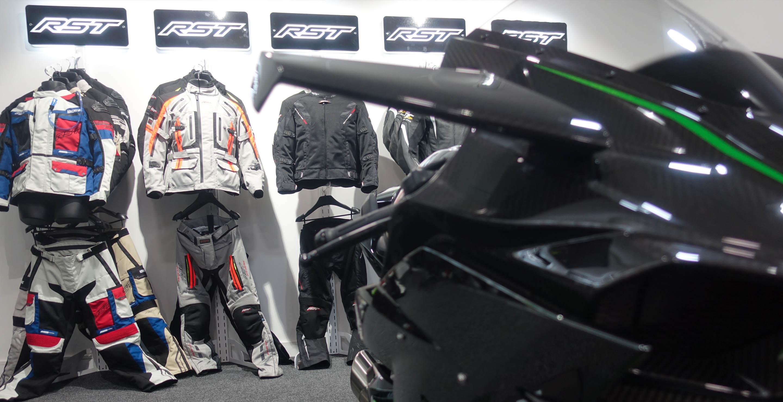 Imagen de acción del Showroom de RST donde se aprecia en un primer plano una moto de atrezzo delante de la colección de chaquetas adventure y urban 2019