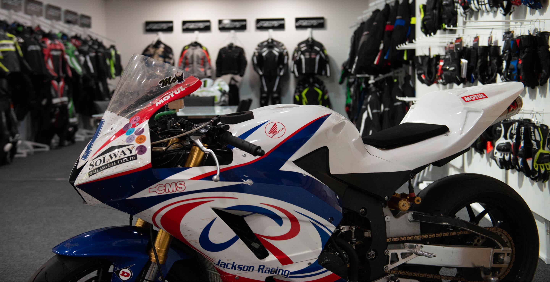 Showroom de RST repleto de chaquetas y motos de pilotos míticos en las instalaciones de RST, durante la visiita de los periodistas españoles