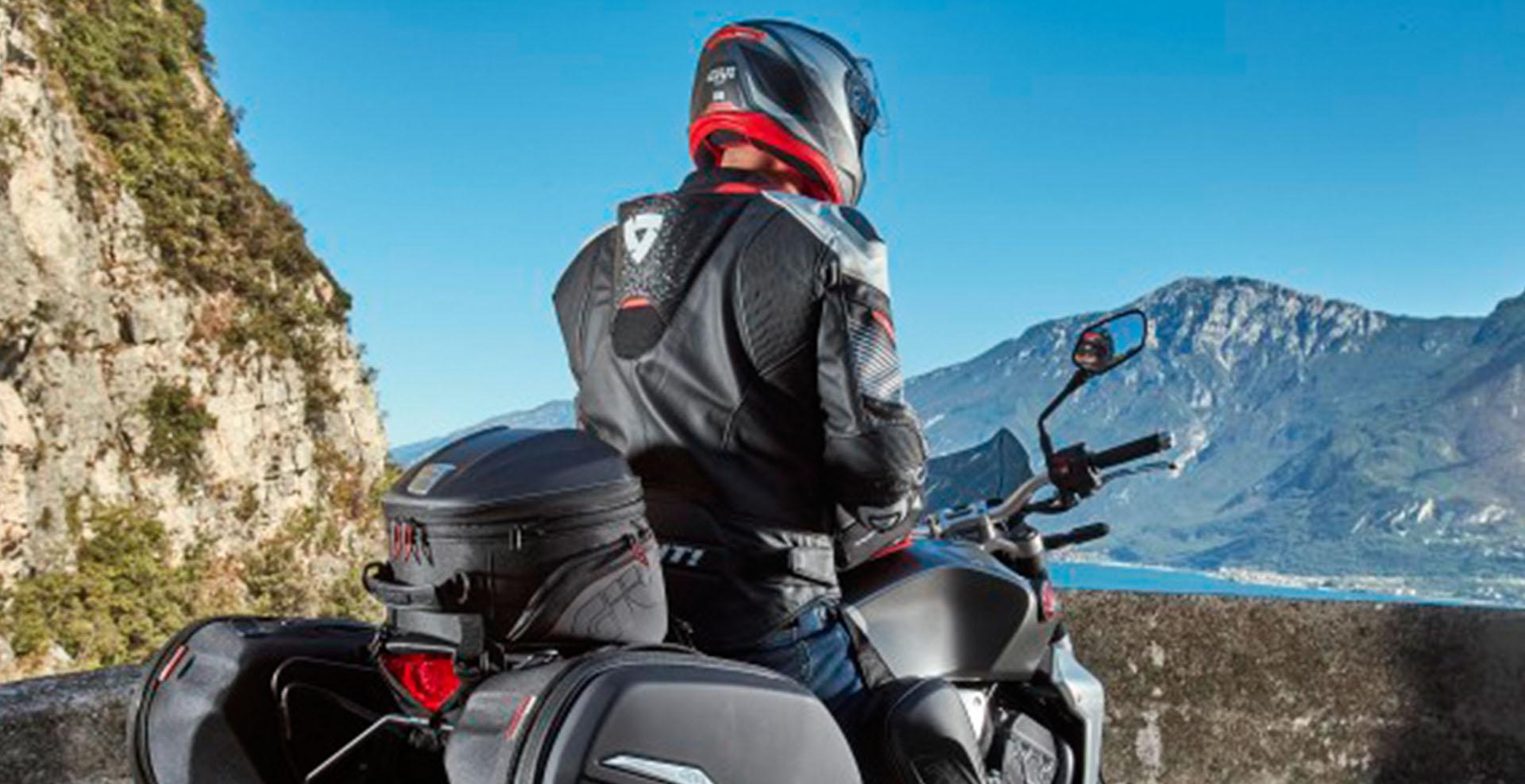 Motorista parado sobre su moto con accesorios GIVI