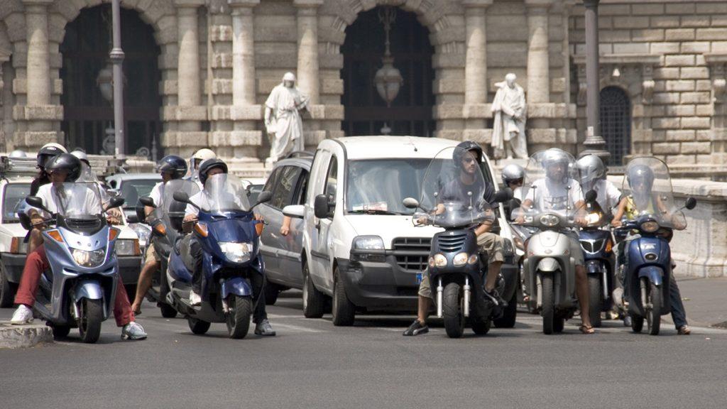 Varias motos paradas en un semáforo delante de los coches