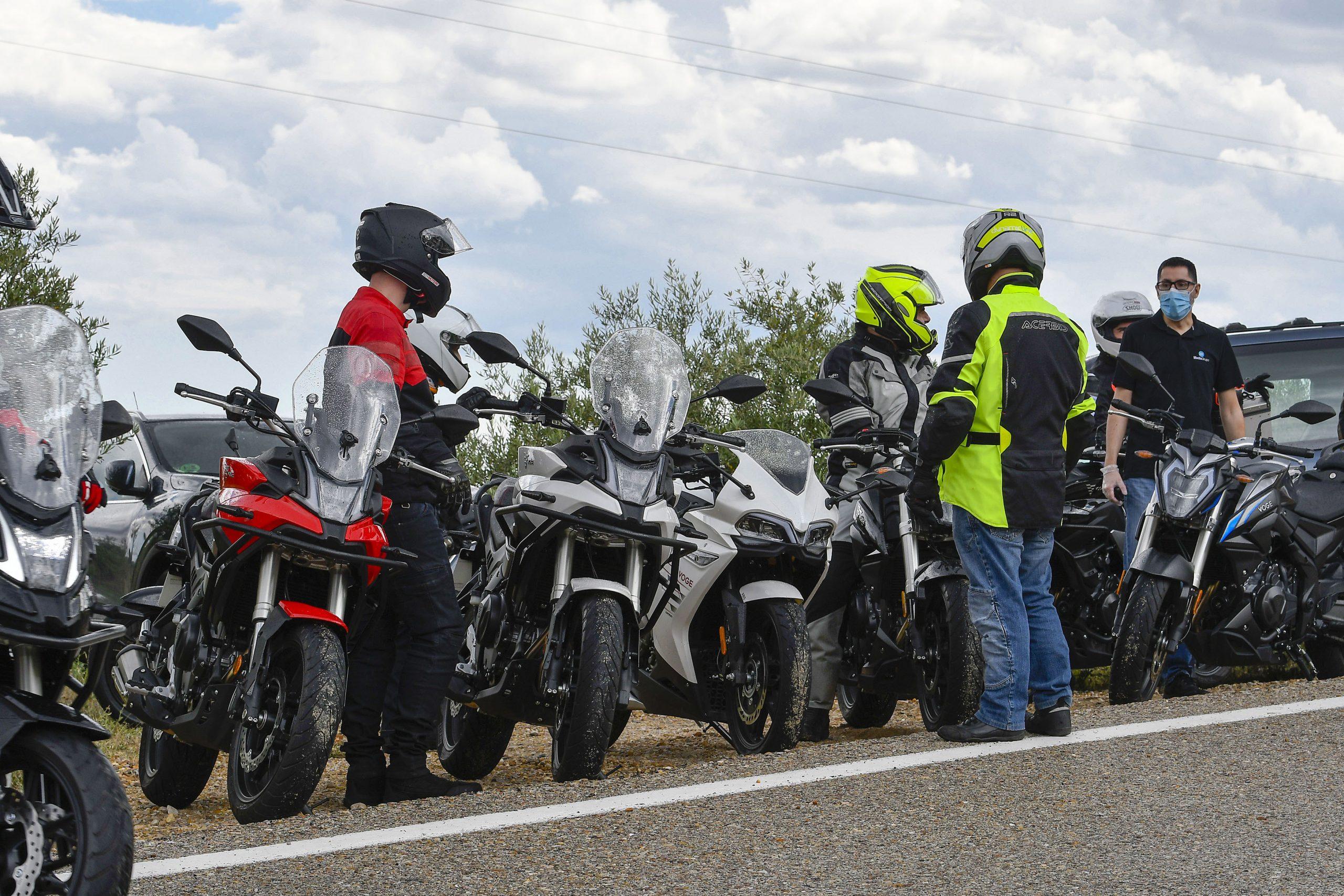 Varios motoristas parados en una presentación de motos