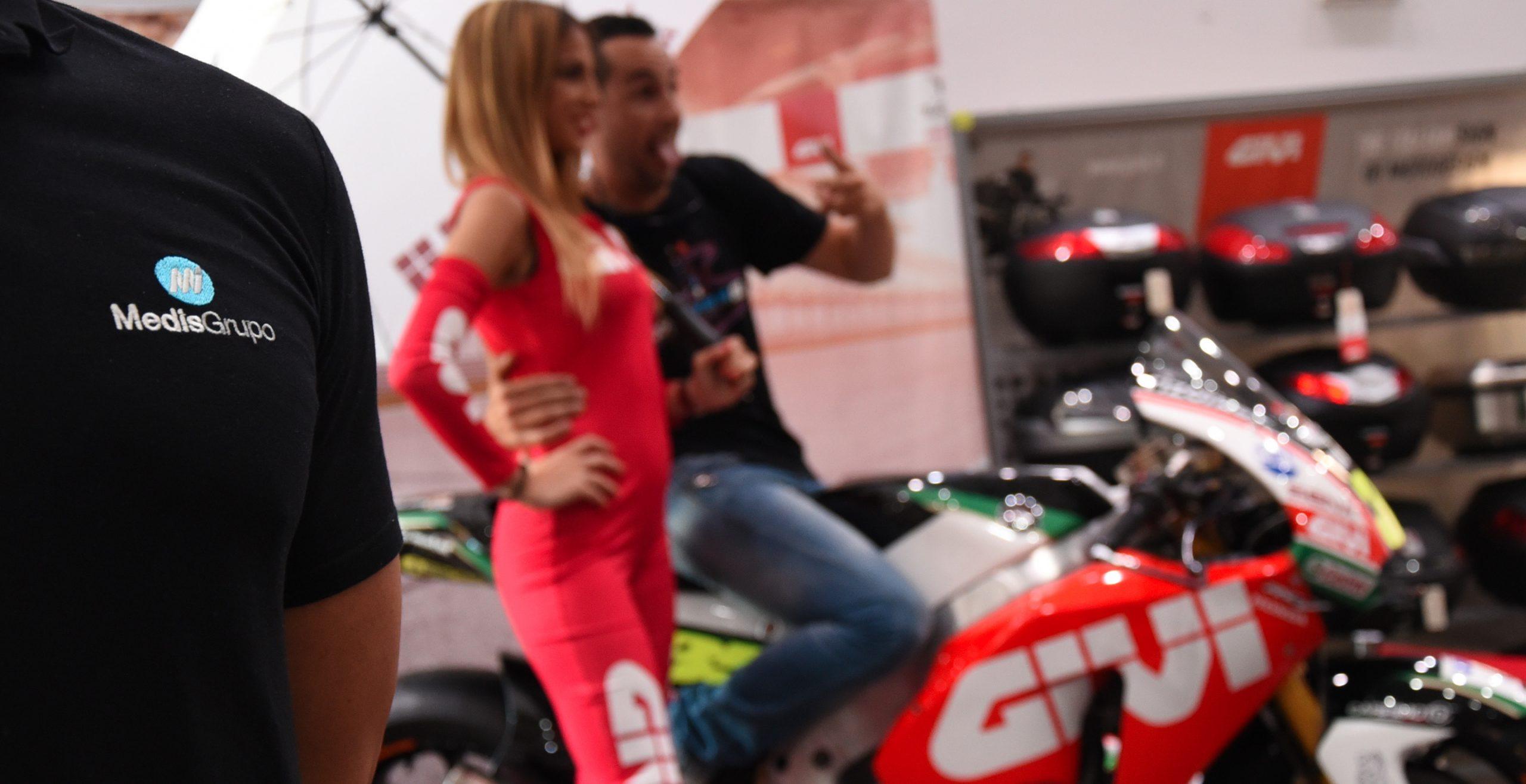 Azafata de GIVI posando al laddo de la moto de Cal Crutchlow del team LCR de MotoGP para acción de marketing de guerrilla GIVI